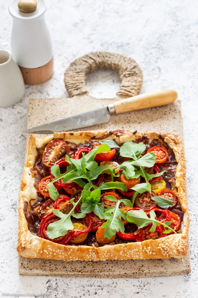 Caramelised Onion Tomato & Capsicum Tart! A fabulous tart to serve over the festive season! The caramelised onions add depth of flavour whilst the cherry tomatoes and capsicum add freshness and texture! Topped with rocket and basil creating a delicious homemade pastry tart everyone will enjoy!