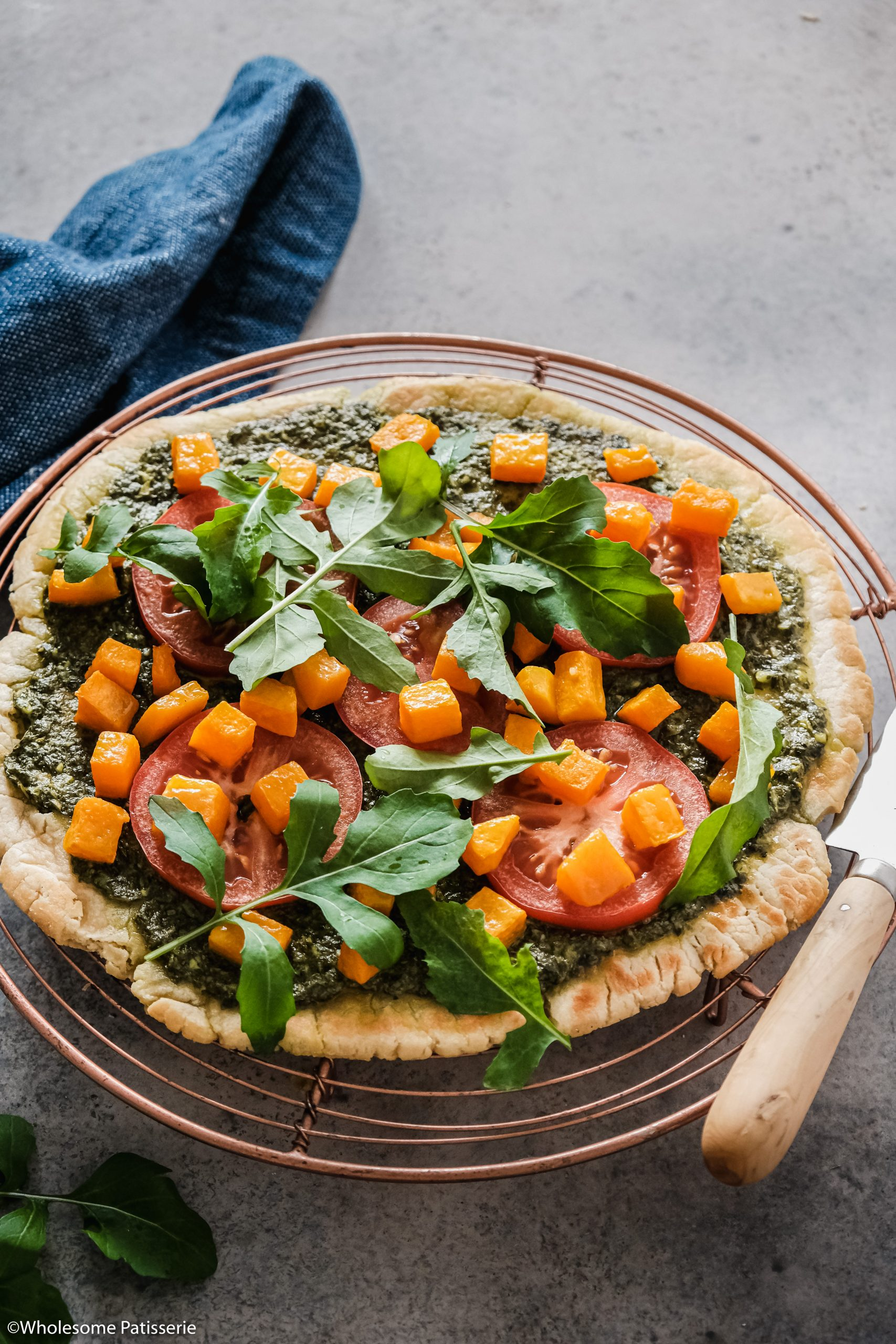 Pesto & Roasted Pumpkin, Tomato Flat Bread! This easy 5-ingredient flat bread whips up in no time, then it's ready for it's toppings! First spread with a spinach and basil pesto, your choice of either store-bought or homemade. I recommend using my Pesto Recipe and halving it, making it the perfect quantity to spread on your flat bread. Then you'll top it with fresh slices of tomato, roasted pumpkin cubed and fresh rocket!