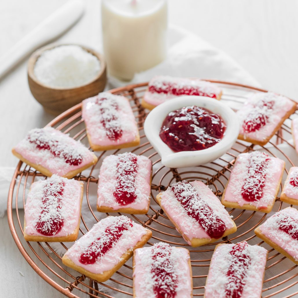 Iced Vovo Biscuits! Delicious biscuits topped with a marshmallow icing, a spread of raspberry jam and a sprinkle of desiccated coconut. These classic Australian biscuits will remind many of their childhoods. They're oh so sweet and a wonderful treat to enjoy.