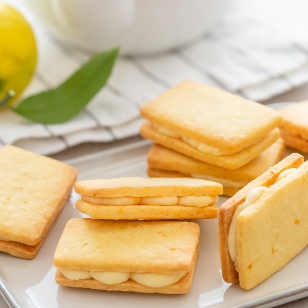 Lemon Cream Shortbread Biscuits! Two layers of melt in your mouth shortbread biscuits filled with a zesty lemon cream. The biscuit dough is created in one bowl then cut into small rectangles and baked. The lemon filling is made with four ingredients and one bowl. Sandwich the biscuits together to create your scrumptious lemon cream shortbread biscuits.