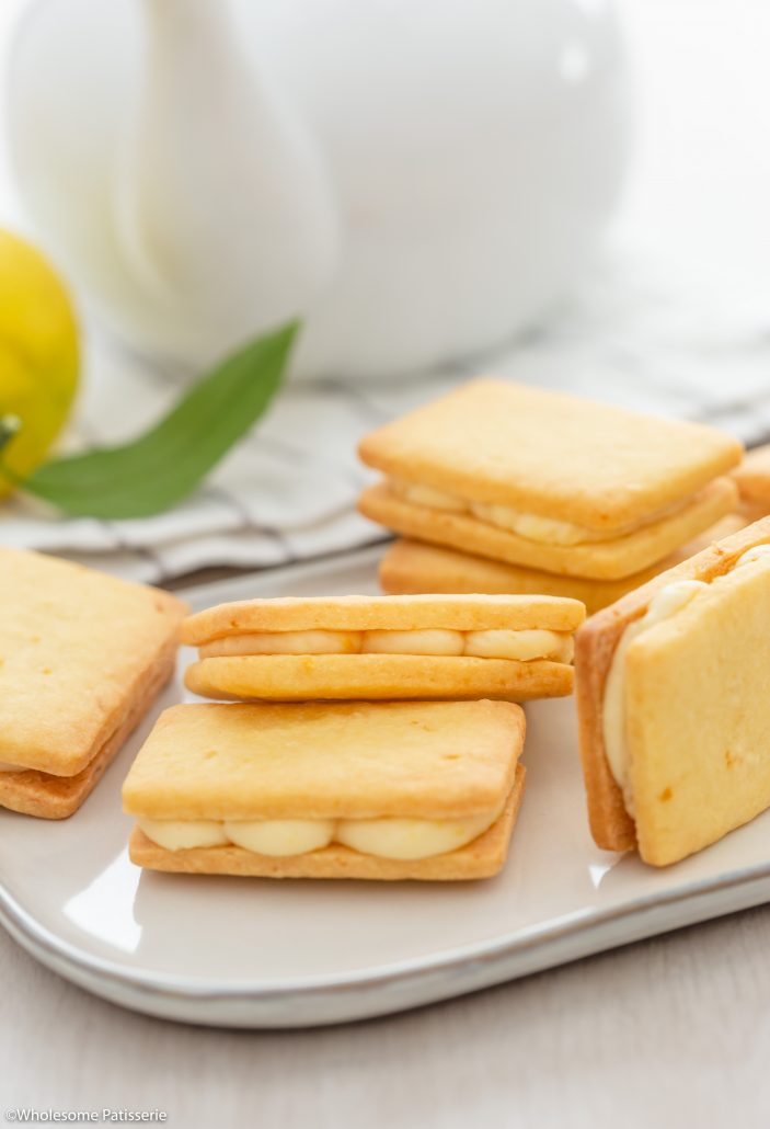 Lemon Shortbread Biscuits! Two layers of melt in your mouth shortbread biscuits filled with a zesty lemon cream. The biscuit dough is created in one bowl then cut into small rectangles and baked. The lemon filling is made with four ingredients and one bowl. Sandwich the biscuits together to create your scrumptious lemon cream shortbread biscuits.