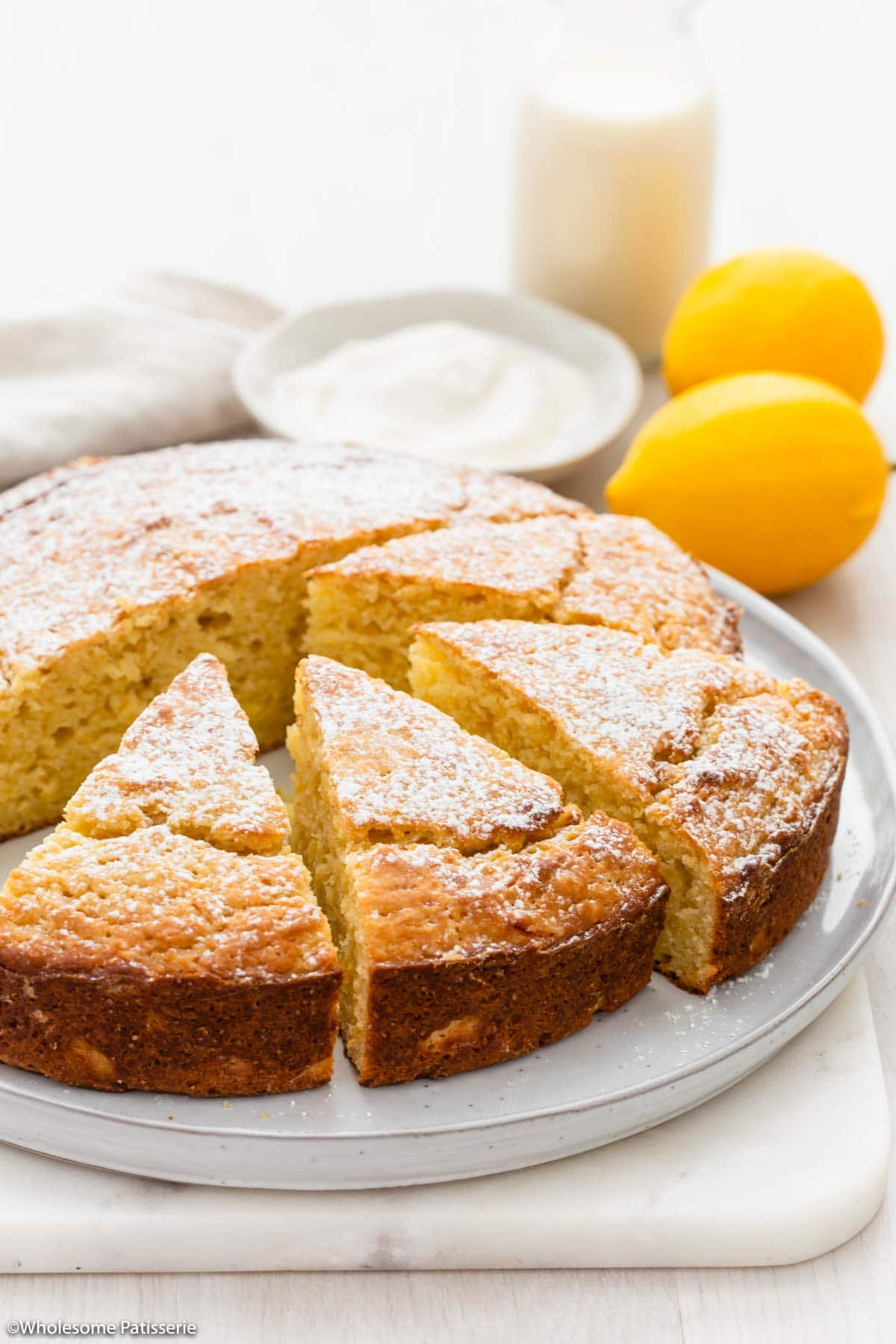 Lemon yoghurt cake dusted with icing sugar and sliced