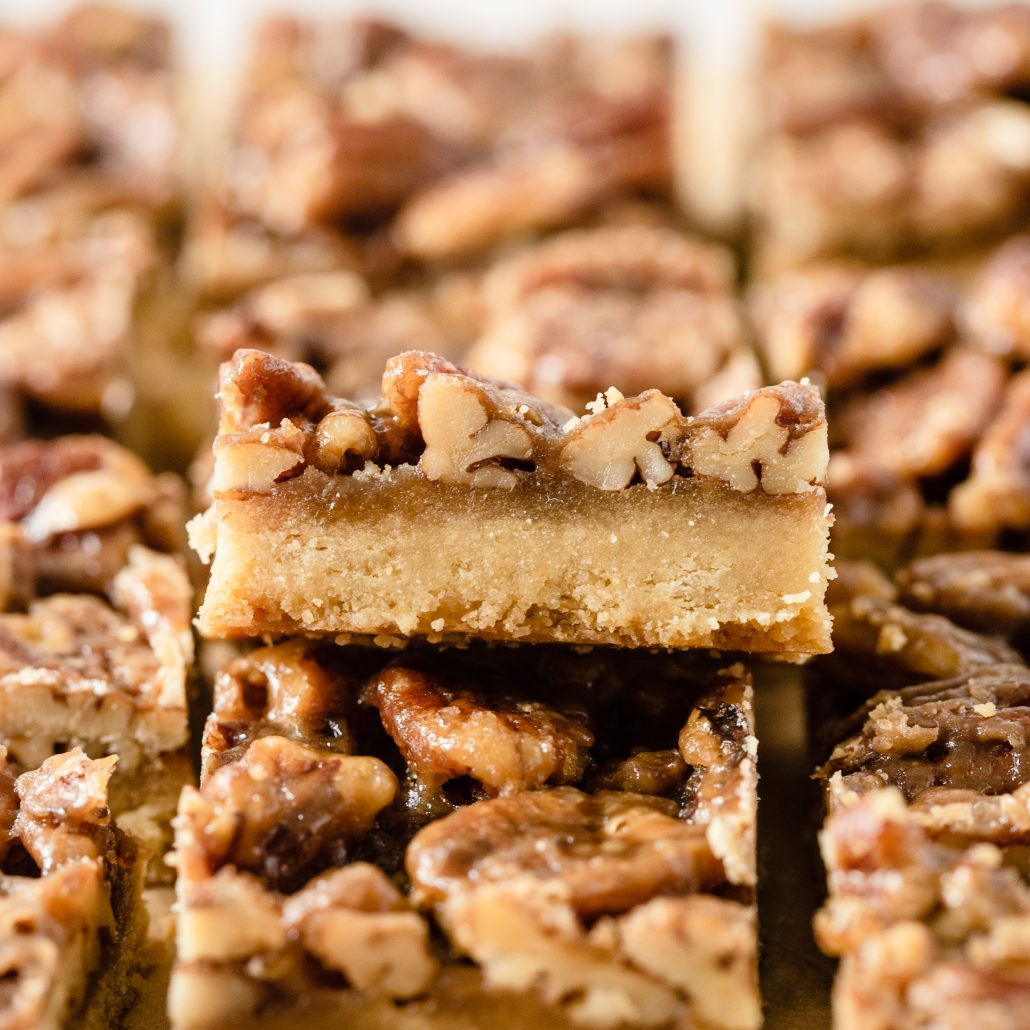 A scrumptious batch of Pecan Pie Bars will satisfy everyones sweet tooth. Created with an easy 4-ingredient shortbread base and an indulgent brown sugar and maple caramel pecan topping. These bars are a take on the traditional pecan pie, a classic and popular American dessert.